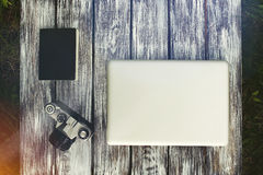 Laptop with notebook and vintage camera. On the background of old boards Royalty Free Stock Photos