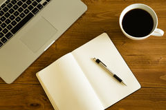 Laptop, notepad and coffee cup on wood table. View from above Royalty Free Stock Images
