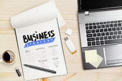 Laptop and notepad with hand drawn business strategy. Royalty Free Stock Photography