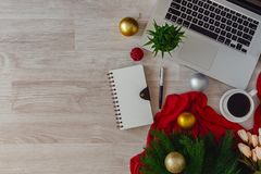 Laptop and notepad with ornaments balls on wood table. Office table on Christmas stock photo