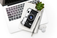 Laptop, notepad, pan, vintage old camera and green flover Royalty Free Stock Images