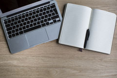 Laptop and Notepad with pen on a wooden Desk. Work. Royalty Free Stock Photography
