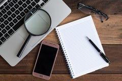 Laptop, Notitieboekje, smartphone, schouwspel en vergrootglas op houten lijst stock foto's