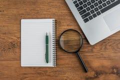Laptop, Notizbuch und Vergrößern und Stift auf Arbeitsschreibtisch Stockfotos