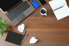 Laptop with office supplies, crumpled paper, green plant and hot black coffee with smoke on vintage grunge wooden desk background Stock Images