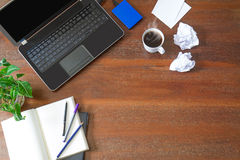 Laptop with office supplies, crumpled paper, green plant and hot black coffee with smoke on vintage grunge wooden desk background Stock Photo