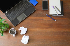 Laptop with office supplies, crumpled paper, green plant and hot black coffee with smoke on vintage grunge wooden desk background Royalty Free Stock Photography