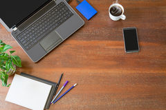 Laptop with office supplies, green plant and hot black coffee with smoke on vintage grunge wooden desk background view from above. Business concept royalty free stock images