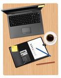 Laptop and office supplies laying on the board Royalty Free Stock Photos