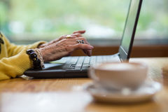 Laptop and old hands. royalty free stock image