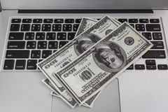 Laptop and one hundred dollar banknotes Royalty Free Stock Images