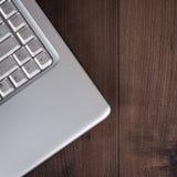 Laptop op bruine houten achtergrond Stock Fotografie