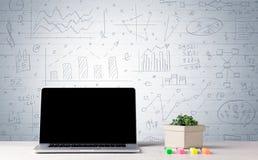 Laptop op bureau met bedrijfsgrafieken op muur Royalty-vrije Stock Afbeeldingen