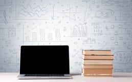 Laptop op bureau met bedrijfsgrafieken op muur Royalty-vrije Stock Afbeelding