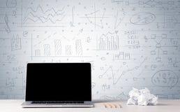 Laptop op bureau met bedrijfsgrafieken op muur Stock Foto's