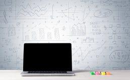 Laptop op bureau met bedrijfsgrafieken op muur Royalty-vrije Stock Foto's