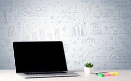 Laptop op bureau met bedrijfsgrafieken op muur Royalty-vrije Stock Foto