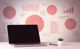 Laptop op bureau met verkoopcirkeldiagrammen Royalty-vrije Stock Afbeelding
