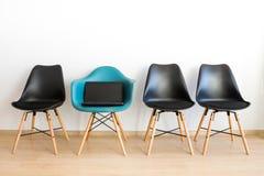 Laptop op een stoel Blauwe stoel onder zwarte op een witte achtergrond stock afbeeldingen