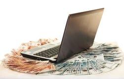 Laptop op grote stapel van rekeningen vijf duizendste Stock Afbeelding