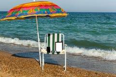 Laptop op het strand, die een telefoon met laptop, technolo zonnebaden Stock Foto