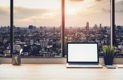 Laptop op lijst in bureauruimte op de achtergrond van de vensterstad, voor de montering van de grafiekvertoning stock foto