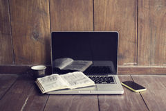 Laptop, open book, cell phone and coffee mug Stock Photography