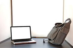 Laptop open op bureau met zak Stock Afbeeldingen