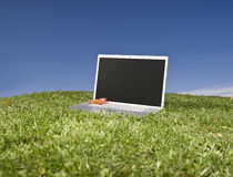 Laptop outdoors on a green field Royalty Free Stock Image