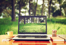 Laptop over wooden table outdoors and blurred background of trees in the forest.  Royalty Free Stock Image