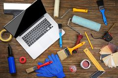 Laptop and paint tools. On wooden table stock image