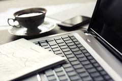 Laptop and paper. Close up of computer with financial statement and cup of coffee Royalty Free Stock Image