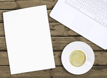 Laptop, paper and cup of coffee with crema Stock Photos