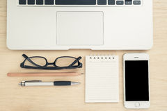 Laptop, paper, mobile phone, pen, pencil and glasses on wooden t Stock Image