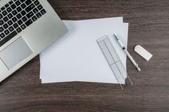 Laptop, paper pen Ruler and Eraser on work desk Royalty Free Stock Images