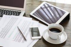 Laptop, pastylka, smartphone i filiżanka z pieniężnym docume, Obrazy Royalty Free
