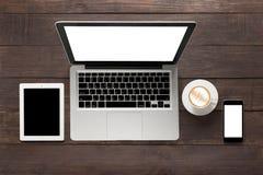 Laptop, pastylka, smartphone i filiżanka kawy na drewnianym backgro, Obrazy Stock