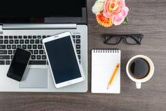 Laptop pastylka z notatnikiem na biurku i telefon komórkowy obrazy stock