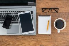Laptop pastylka z notatnikiem na biurku i telefon komórkowy zdjęcie stock