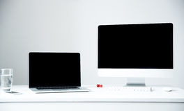 Laptop and PC on the workplace in office Stock Images