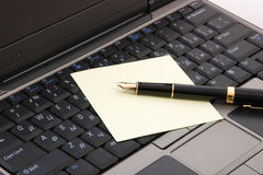 Laptop and pen Stock Photography