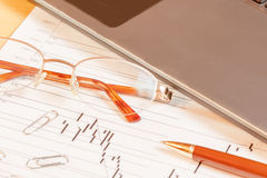 Laptop, pen and glasses on office desk. Selective focus Stock Photos