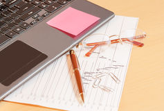 Laptop, pen and glasses on office desk. Selective focus on glass Stock Image