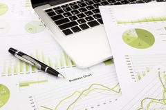 Laptop and pen with green business charts, graphs, information a Stock Photos