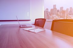 Laptop and pen on notepad for agenda kept on table in empty corporate conference room with cityscape view on background. Selected focus on notepad royalty free stock image