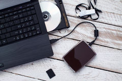 Laptop with pendrive, sd card, CD and portable hard drive. Concept of data storage Royalty Free Stock Photography