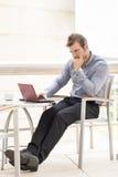 Laptop pensativo do homem de negócios. fotografia de stock royalty free