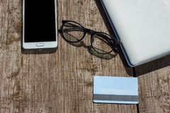 Laptop phone glasses and credit card lie on wooden background royalty free stock photo