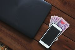 Laptop, phone and money on wooden background. royalty free stock photos