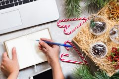 Laptop, phone, notebook, women`s hands, Christmas decorations - concept planning holidays. View from above Stock Photos